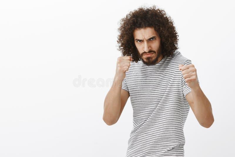 愤怒的恶霸室内射击有胡子和非洲的理发的,站立在与被举的握紧拳头的拳击姿势,皱眉 库存照片