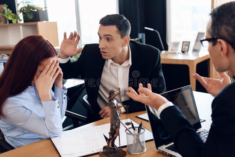愤怒的成人人举了他的在坐在律师`局的红发妇女的手 免版税库存照片