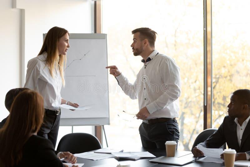 愤怒的男女同事在公司团队会议上争论 免版税库存图片