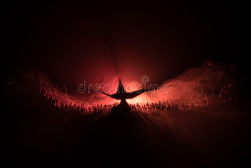 愿望灯  人大人群的剪影站立反对愿望一盏大灯的与被定调子的光束的在有雾的backgr 免版税库存图片