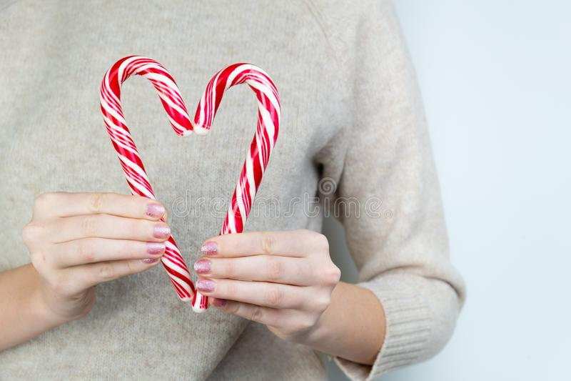 慈善概念:人拿着做形状的两个棒棒糖心脏 库存照片