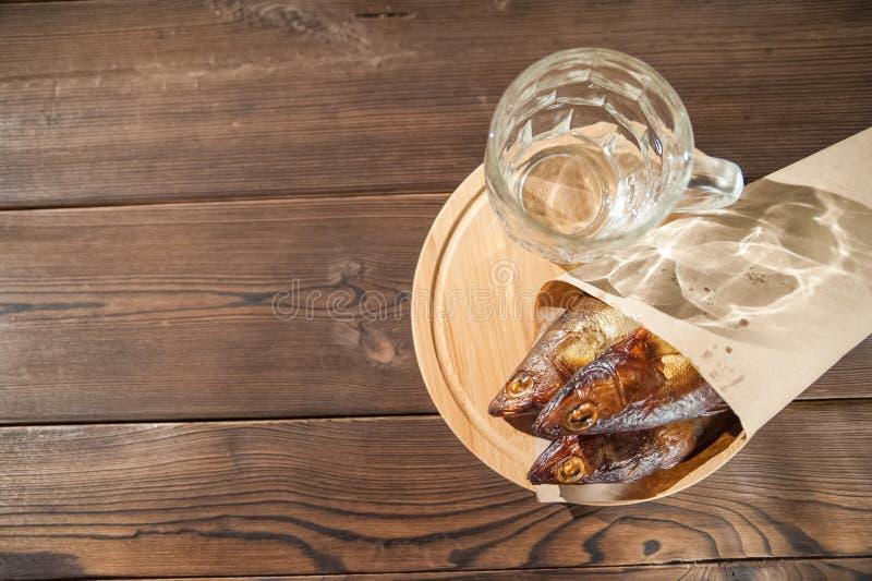 慕尼黑啤酒节假日概念 啤酒,熏制的鱼,在木质地背景的芯片在一把黑暗的钥匙 在玻璃的啤酒,在pape的鱼 库存图片