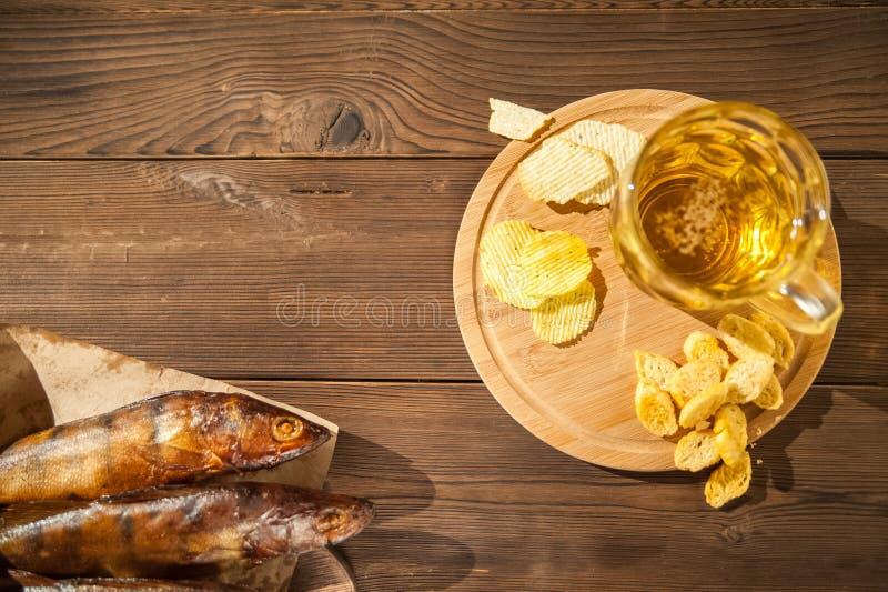 慕尼黑啤酒节假日概念 啤酒,熏制的鱼,在木质地背景的芯片在一把黑暗的钥匙 在玻璃的啤酒,在pape的鱼 免版税库存照片