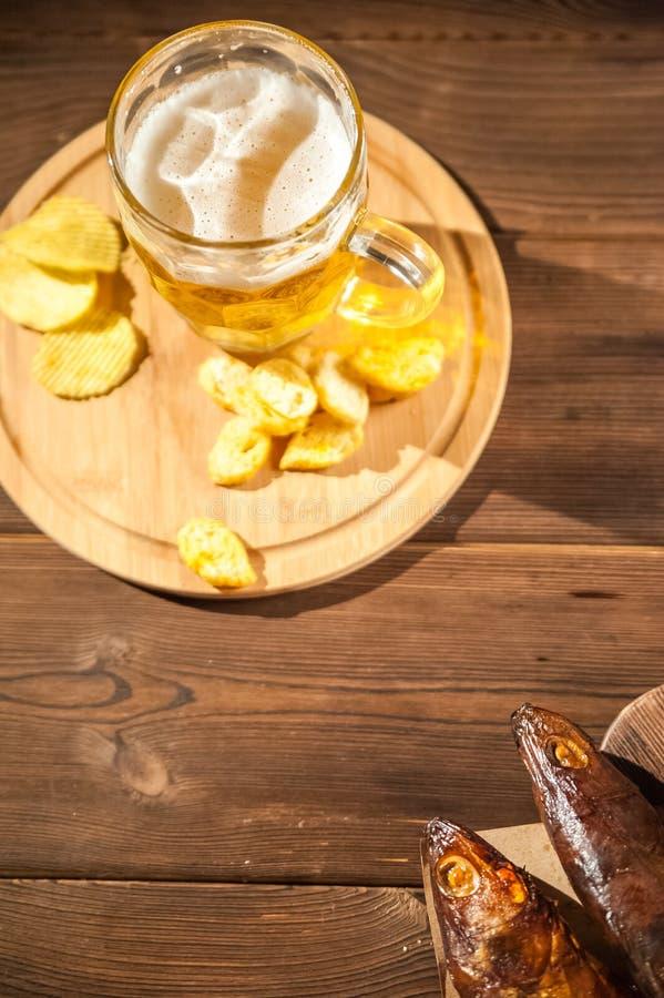 慕尼黑啤酒节假日概念 啤酒,熏制的鱼,在木质地背景的芯片在一把黑暗的钥匙 在玻璃的啤酒,在pape的鱼 免版税库存图片