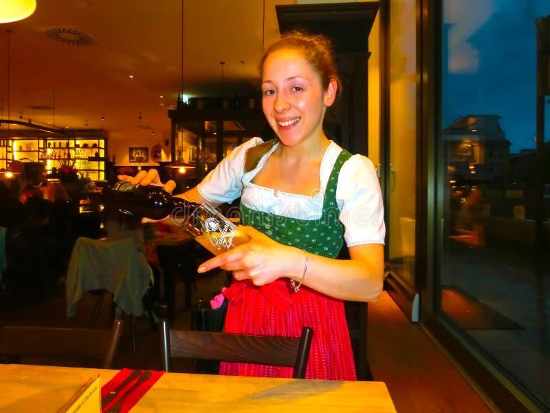慕尼黑,德国- 2017年5月01日:作为女王/王后的少妇传统巴法力亚Tracht的在餐馆或客栈Stubn与 免版税库存图片
