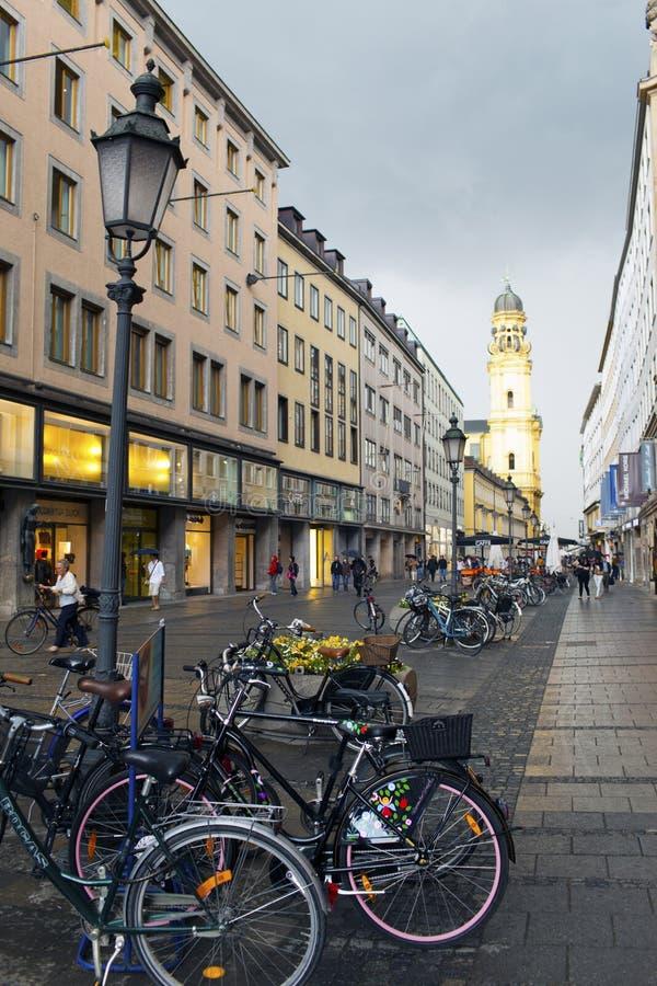 慕尼黑,德国- 2012年5月29日:在街道Theatinerstrasse上的自行车有在圣Cajetan Theatine教会的看法  免版税库存图片