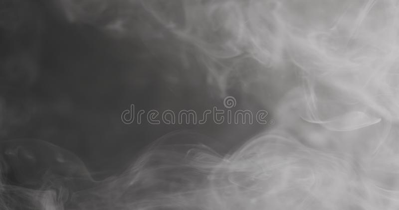 慢动作漂浮在黑背景的空气的特写镜头蒸气 库存图片