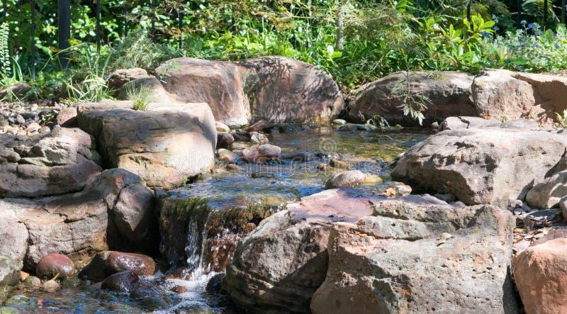 翻滚慢慢地反对与密集的绿色叶子的岩石的瀑布 图库摄影