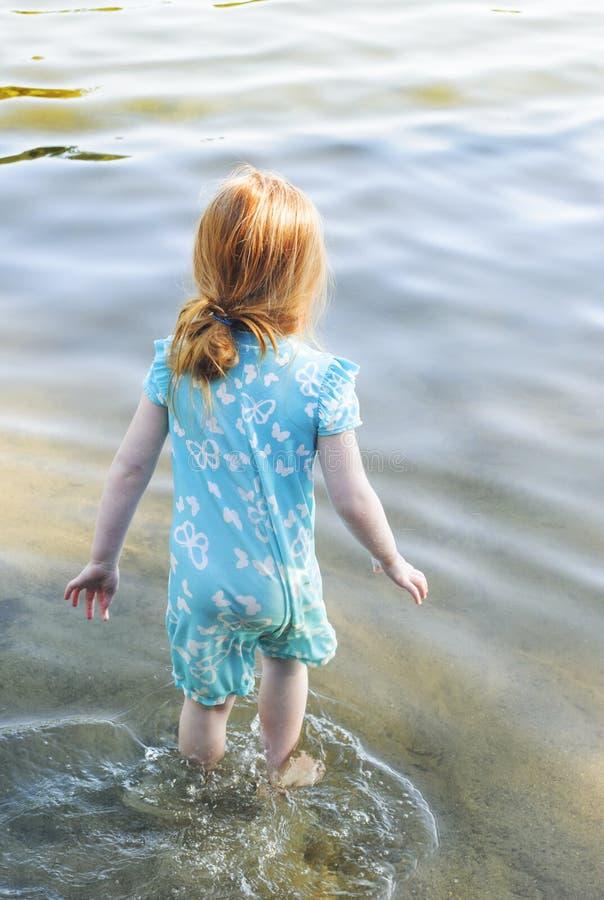 慢慢地走入未知的水的小女孩 库存图片
