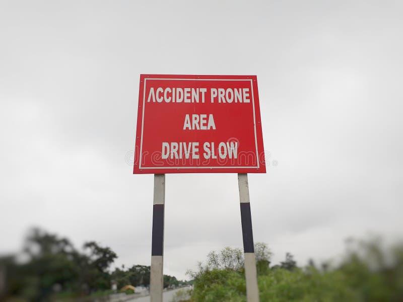 慢的驱动,在高速公路的易出事故的区域标志板,路旁 图库摄影