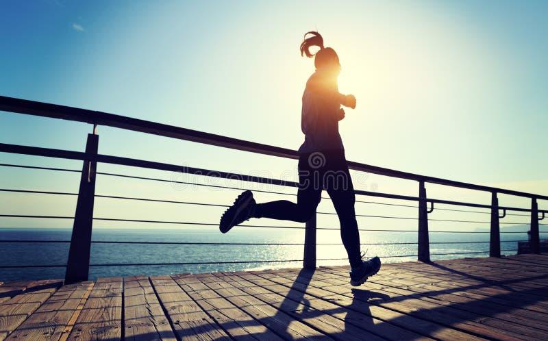 慢跑者在海边木板走道的早晨锻炼在日出期间 图库摄影