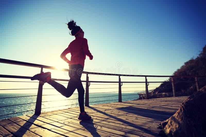 慢跑者在海边木板走道的早晨锻炼在日出期间 免版税库存照片