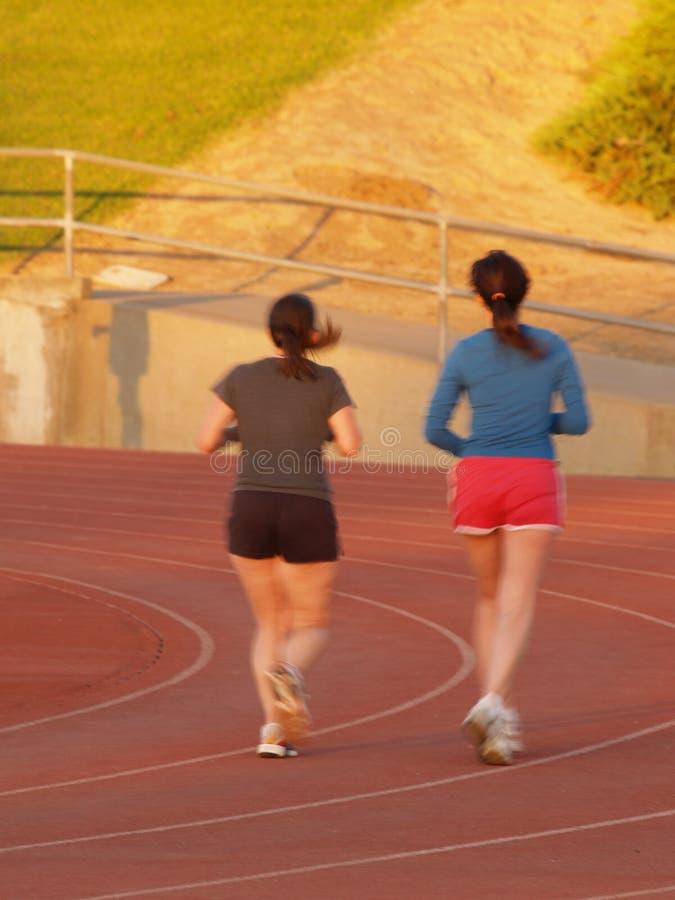 慢跑者跟踪妇女 免版税库存图片