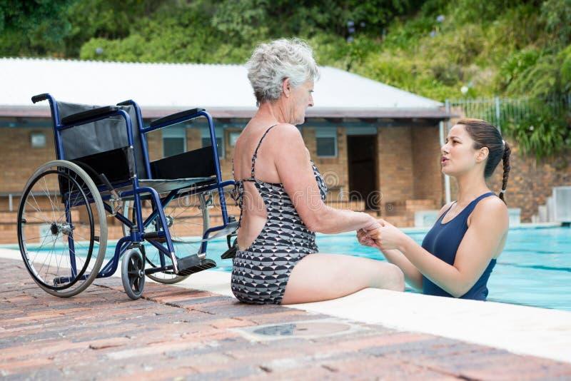 慰问一名残疾资深妇女的游泳教练 免版税库存图片