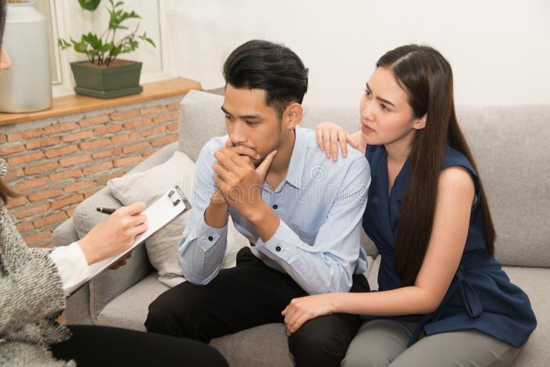 慰问他的丈夫的亚裔妇女坐有心理学家的长沙发 免版税图库摄影