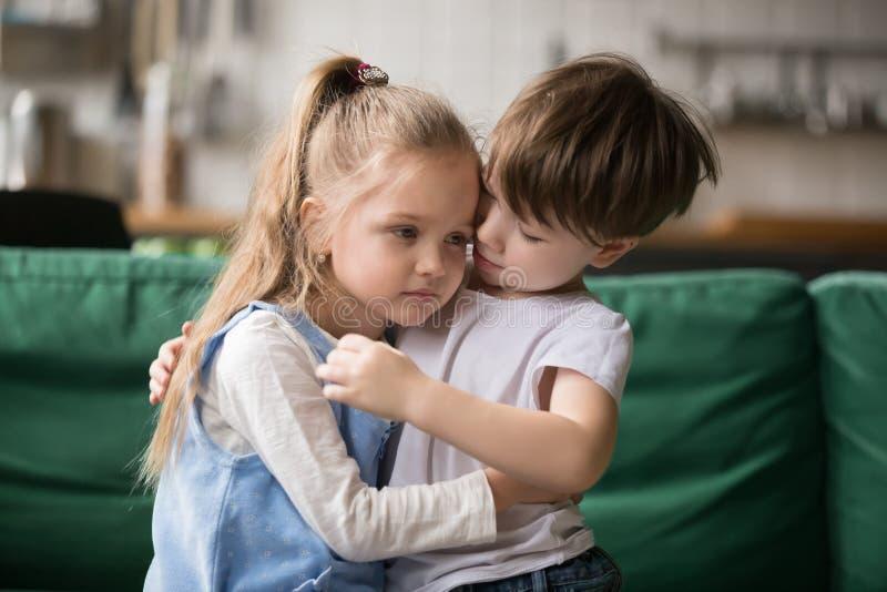 慰问和支持生气女孩拥抱的小男孩兄弟 库存图片
