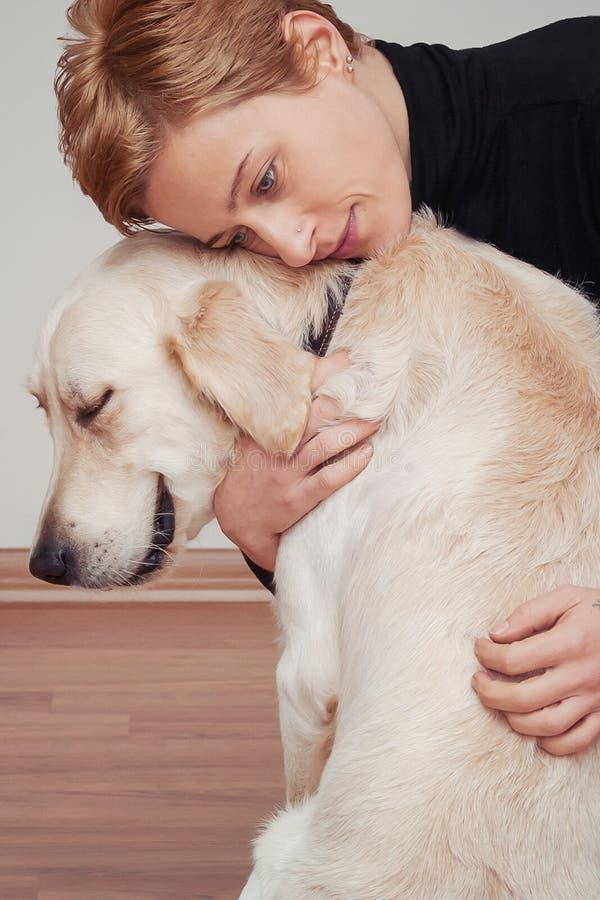 慰问并且解除,少妇拥抱她的狗 免版税库存照片