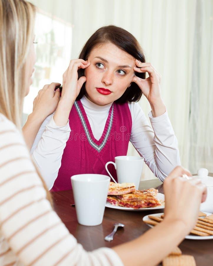 慰问沮丧的女孩的少妇 免版税库存图片