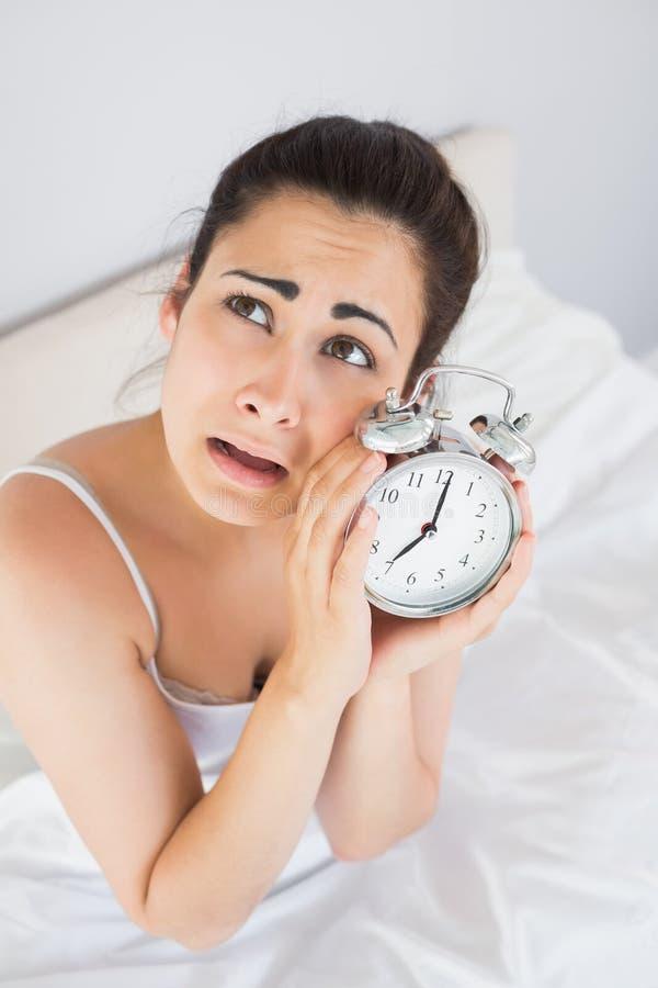 懊恼妇女在床上的拿着一个闹钟 库存图片