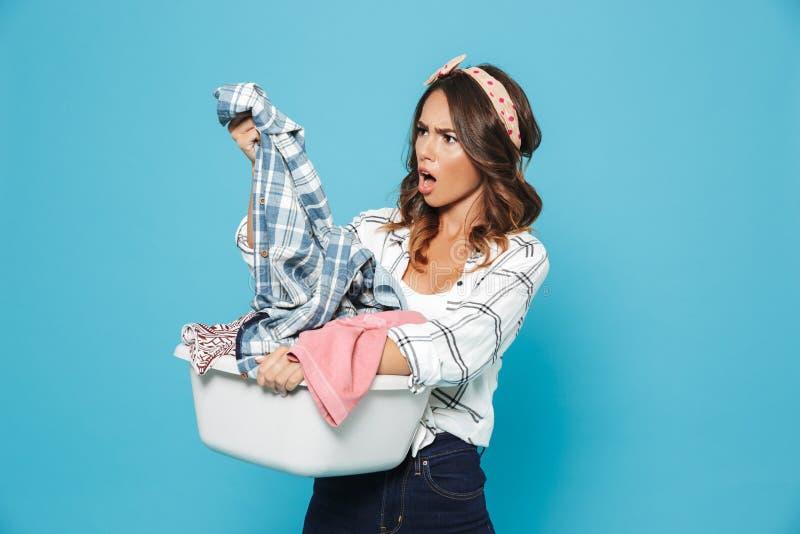 懊恼深色的主妇20s运载的洗衣篮照片  免版税图库摄影