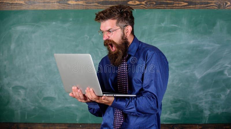 懊恼由慢互联网 使他困恼的慢互联网 老师有胡子的人现代膝上型计算机黑板背景 行家 图库摄影