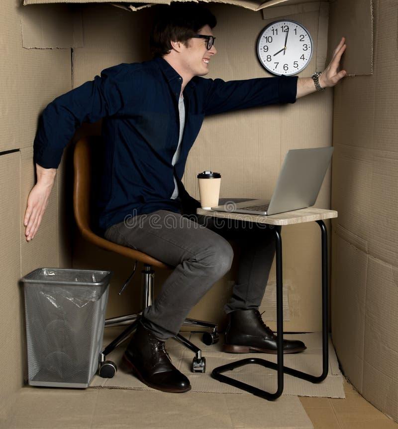 懊恼经理感觉在小纸盒室里面的难受 免版税库存照片