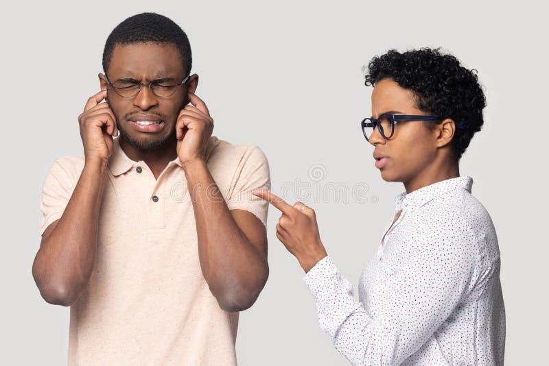 懊恼黑人避免打扰种族女性演讲 免版税图库摄影