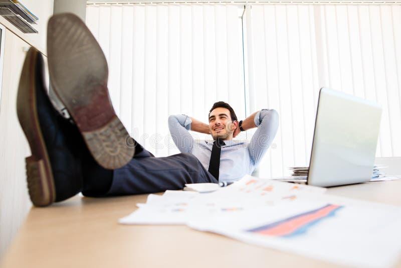 懒惰商人在书桌上把他的腿放 免版税库存图片