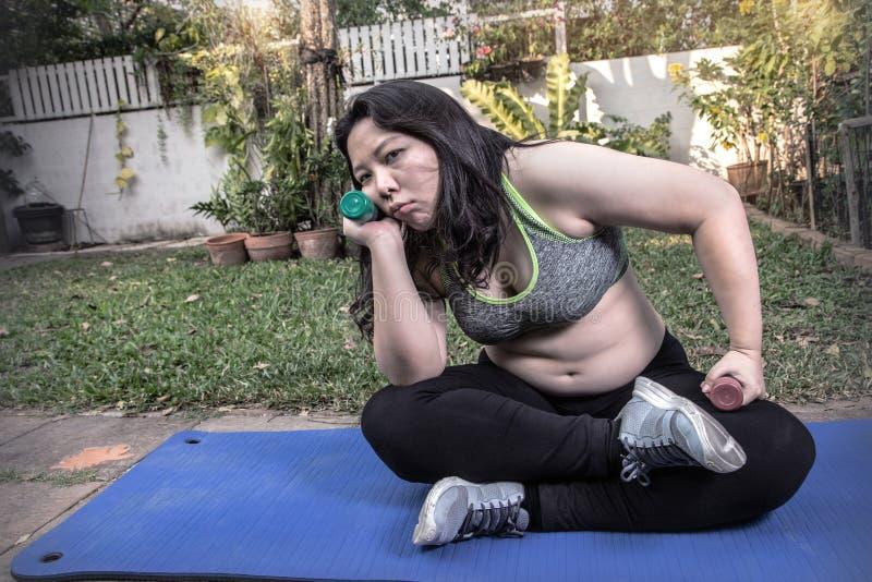 懒惰肥胖妇女疲倦了锻炼举行哑铃的乏味面孔手放弃锻炼概念 免版税库存照片