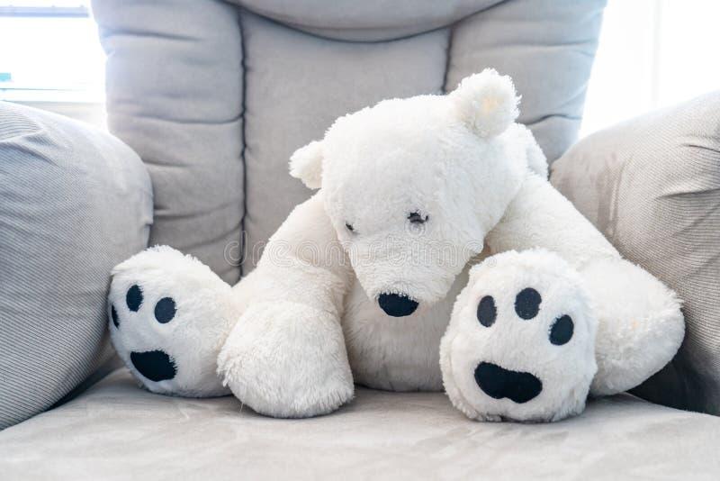 懒散在一把豪华的灰色托儿所椅子的白色玩具熊 由后照与自然阳光 免版税库存图片