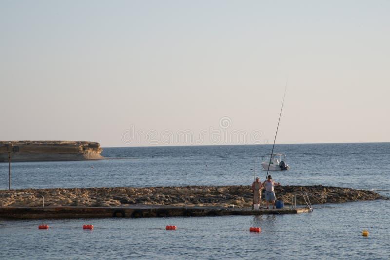 戈佐岛,马耳他- 2019年7月04日:抓鱼的两位渔夫在海岸 库存图片