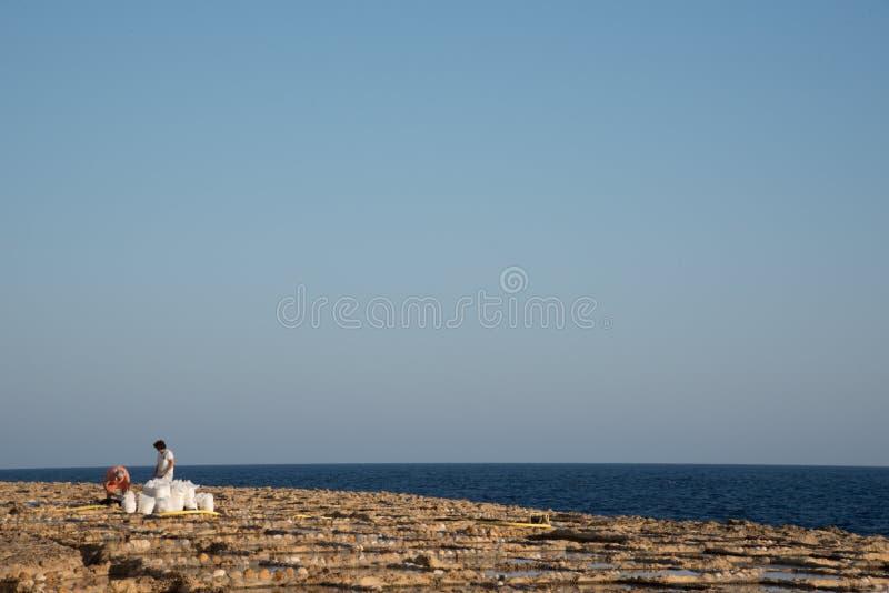 戈佐岛,马耳他- 2019年7月04日:收获从盐平底锅的盐 免版税库存图片