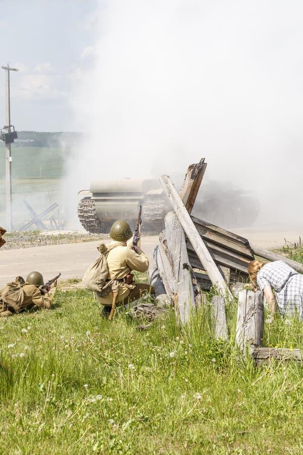 戏剧化 拿着步枪的巨大爱国战争的战士 很多烟 有平民 免版税库存图片