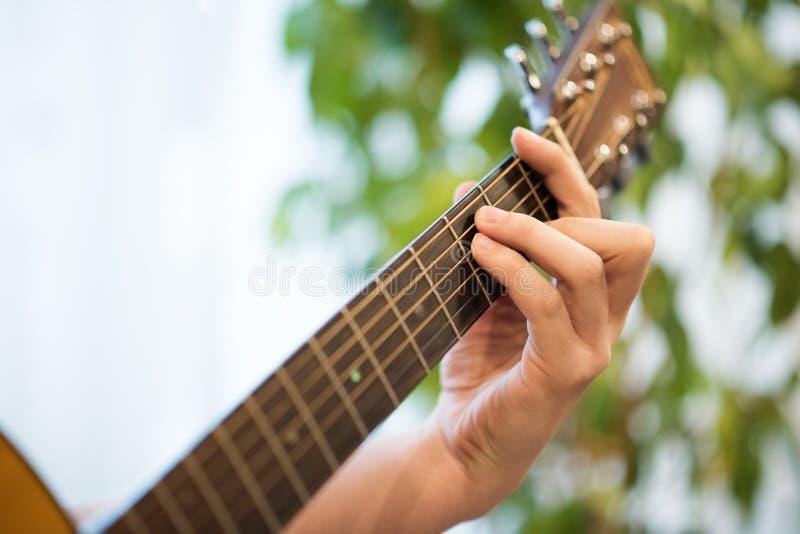 戏剧声学吉他特写镜头 吉他fretboard用男性手 库存照片