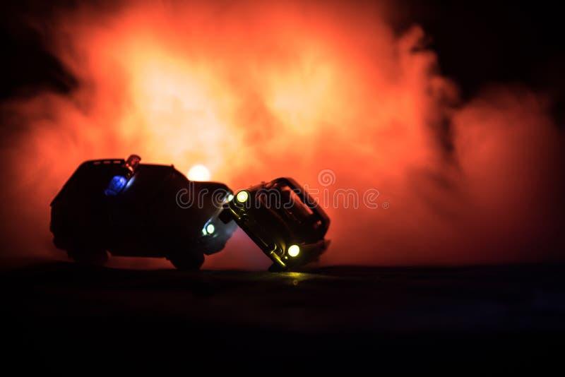 戏弄丰田FJ追逐Ford Thunderbird汽车的巡洋舰汽车在晚上有雾背景 玩具在桌上的装饰场面 - 1月11日2日 免版税库存照片