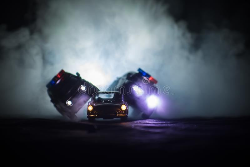 戏弄丰田FJ追逐Ford Thunderbird汽车的巡洋舰汽车在晚上有雾背景 玩具在桌上的装饰场面 - 1月11日2日 图库摄影