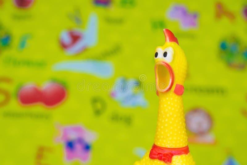 戏弄在迷离玩具背景的橡胶尖叫声黄色鸡在杂乱 免版税库存图片