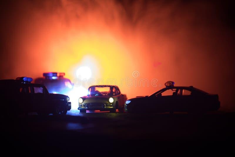 戏弄追逐Ford Thunderbird汽车的BMW警察和丰田FJ巡洋舰汽车在晚上有雾背景 玩具在选项的装饰场面 图库摄影