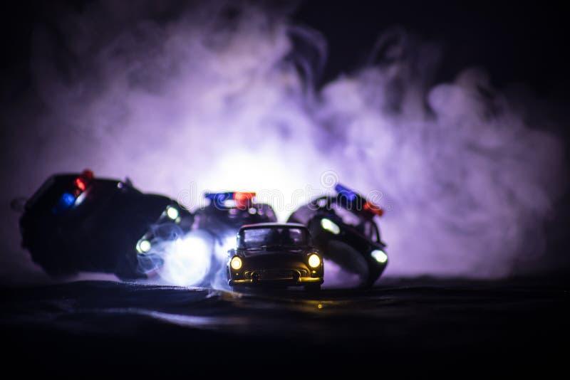 戏弄追逐Ford Thunderbird汽车的BMW警察和丰田FJ巡洋舰汽车在晚上有雾背景 玩具在选项的装饰场面 免版税库存照片