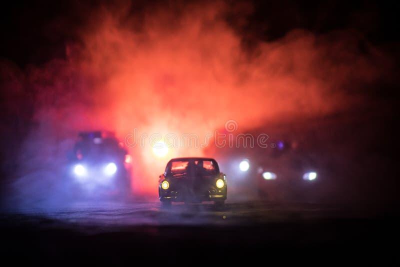 戏弄追逐Ford Thunderbird汽车的BMW警察和丰田FJ巡洋舰汽车在晚上有雾背景 玩具在选项的装饰场面 库存图片