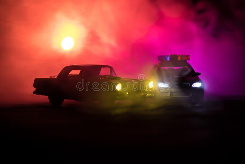 戏弄BMW追逐Ford Thunderbird汽车的警车在晚上有雾背景 玩具在桌上的装饰场面 选择聚焦- 免版税图库摄影