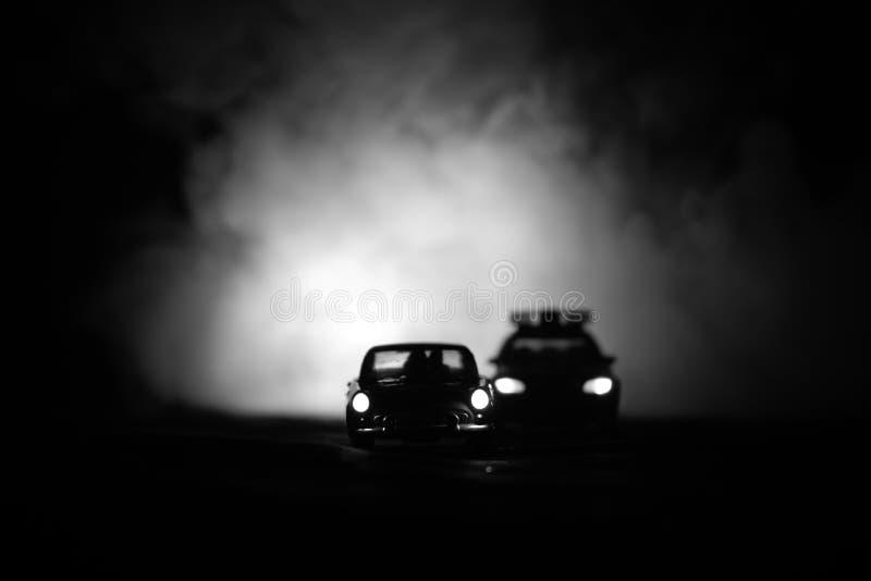 戏弄BMW追逐Ford Thunderbird汽车的警车在晚上有雾背景 玩具在桌上的装饰场面 选择聚焦- 库存照片