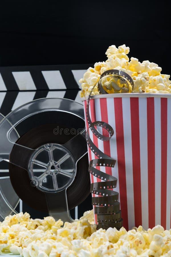 戏院广告概念:玉米花和影片在黑暗的背景 免版税库存照片
