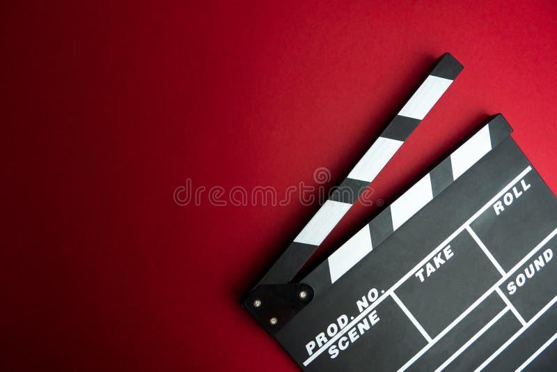 戏院最小的概念 在戏院的观看的影片 在红色背景的拍板 免版税库存图片