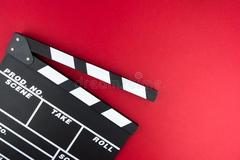 戏院最小的概念 在戏院的观看的影片 在红色背景的拍板 免版税库存照片