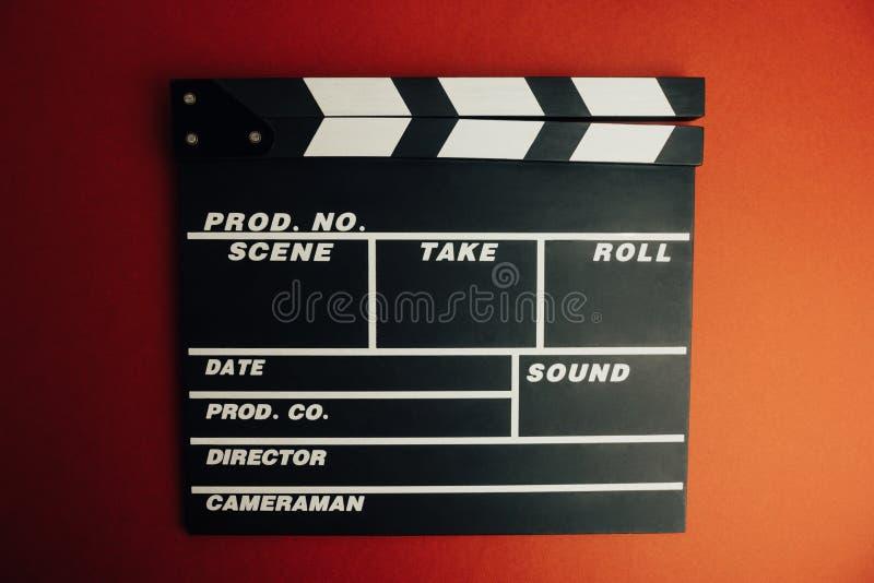 戏院最小的概念 在戏院的观看的影片 在红色背景的拍板 库存照片