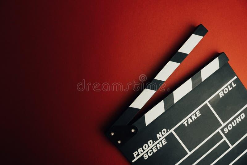 戏院最小的概念 在戏院的观看的影片 在红色背景的拍板 图库摄影