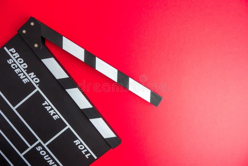 戏院最小的概念 在戏院的观看的影片 在红色背景的拍板 库存图片