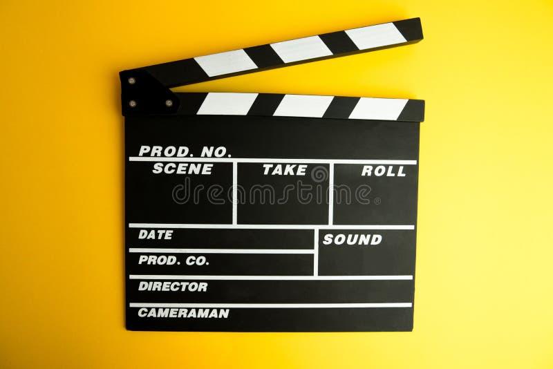 戏院最小的概念 在戏院的观看的影片 在黄色背景的拍板 免版税库存图片
