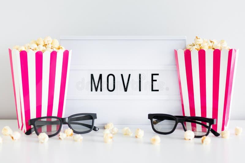 戏院概念-镶边箱子用玉米花、3d玻璃和灯箱有电影词的 图库摄影